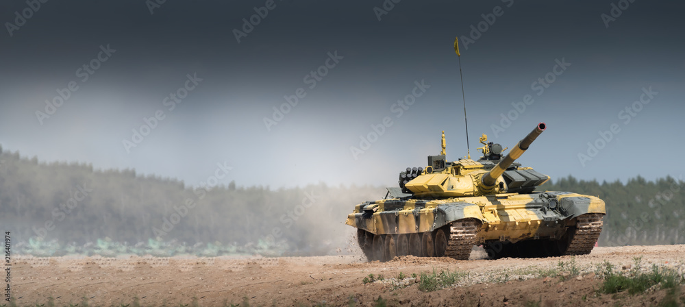 Fototapeta Military or army tank ready to attack and moving over a deserted battle field terrain. a lot of dust. copyspace