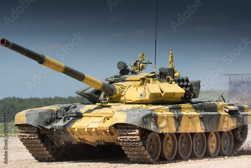 Leinwand Poster Military or army tank ready to attack and moving over a deserted battle field terrain