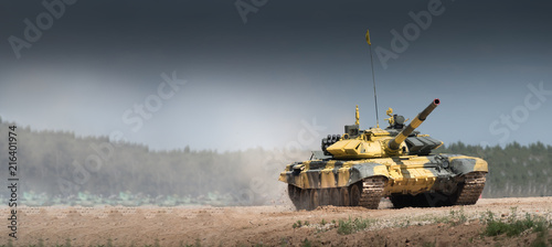 Military or army tank ready to attack and moving over a deserted battle field terrain Wallpaper Mural