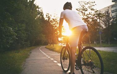 Mladi momak u ležernoj odjeći vozi bicikl na cesti u večernjem gradu