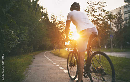 Photo sur Toile Cyclisme The young guy in casual clothes is cycling on the road in the evening city