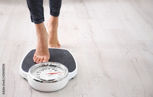 Photo Woman measuring her weight using scales on floor