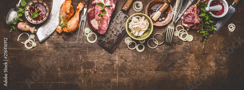 Various grill an bbq meats on rustic wooden background with aged kitchen and but Fototapete