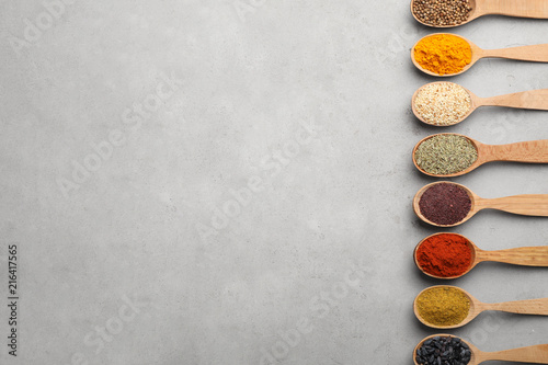 Flat lay composition with different aromatic spices in wooden spoons on gray background
