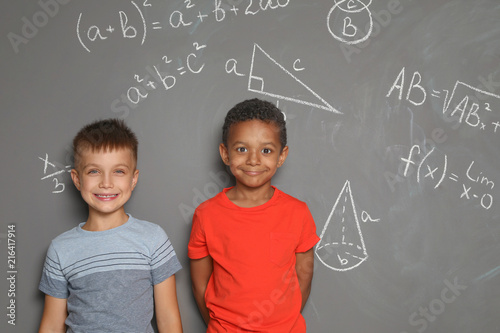 Little school children and mathematical formulas on grey background