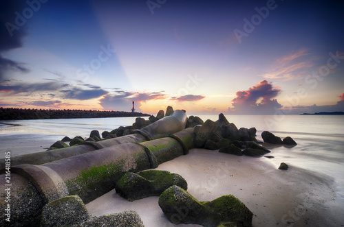 Papiers peints Morning Glory Stunning sunrise on the tropical sandy beach. mossy pipe line and lighthouse background with sunlight ray of light