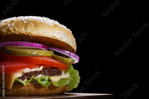 Delicious tasty burger, isolated on black background