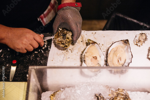 Chef shucking a fresh oyster with knife and stainless steel mesh oyster glove.