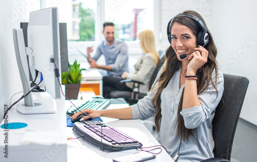 Canvas Print Portrait of happy smiling female customer support phone operator at workplace