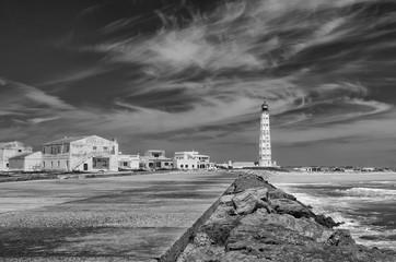 Portugalia, wyspa Farol. Falochron, biała latarnia morska.