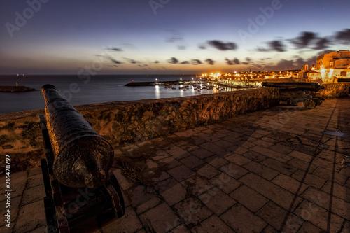 Staande foto Chocoladebruin Paisaje del atardecer sobre el puerto desde los cañones de la muralla de Sines en Portugal