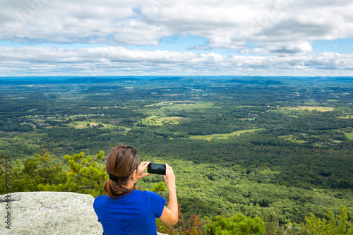 Fotografia, Obraz Woman takes a snpashot of the Hudson Valley farm land from Gertrude's Nose hikin