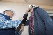 Builders Looking At Peeling Paint On An Interior Ceiling
