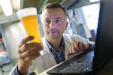 Brewer In Uniform Tasting Beer