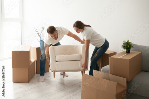 Young couple carry chair to new living room after moving in ...