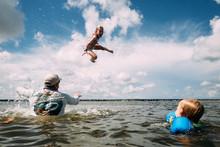 Man Throwing Girl In Air In Ocean