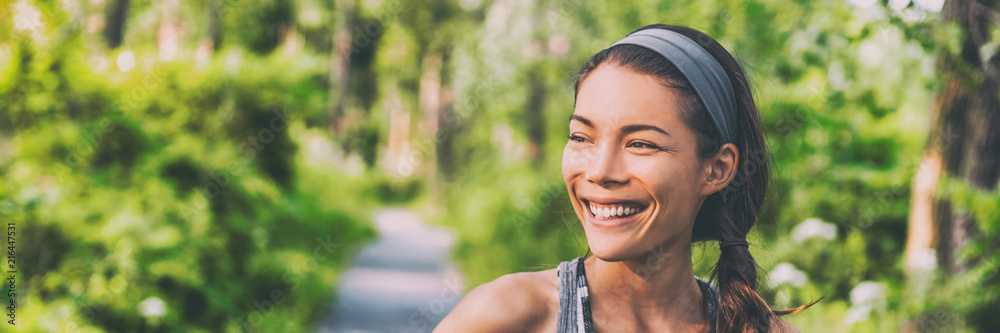 Fototapeta Happy young Asian woman outdoor walking in park smiling living an active and healthy lifestyle. Panoramic banner background.
