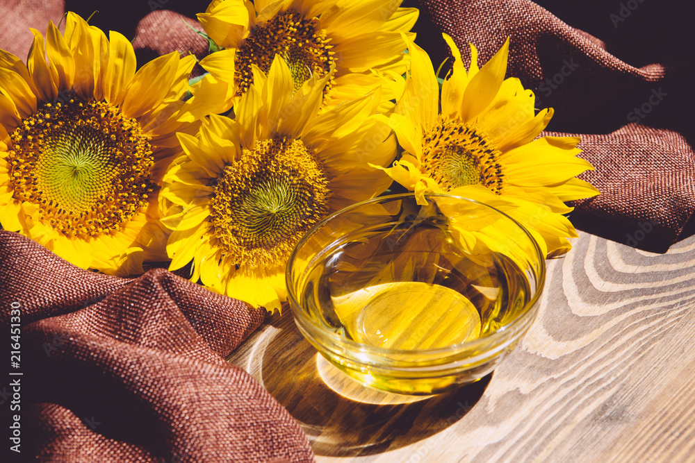 Fototapety, obrazy: Sunflower oil with sunflowers on wooden background