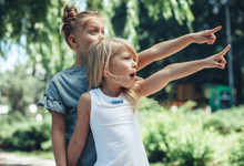 Look. Side View Of Amazed Children Standing In Park And Pointing Fingers. Older Girl Is Behind Younger One. They Are Happy And Content