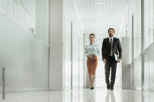 Stampa su Tela Full length portrait of serious woman and orderly unshaven male worker moving in