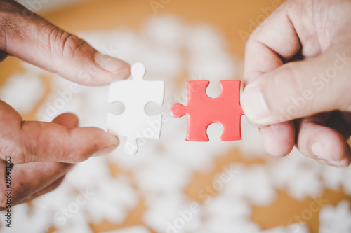 Fototapety, obrazy: Hands of business people hold paper jigsaw puzzle and solving puzzle together,Business team assembling Jigsaw puzzle,Business group wanting to put pieces of puzzle together.