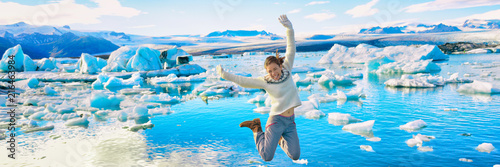 mata magnetyczna Iceland Jökulsárlón Glacier Lagoon tourist woman jumping of happiness - Icelandic touristic destination popular attraction. Panoramic banner.