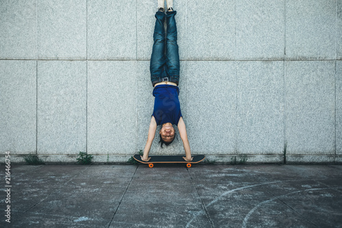 Fotografia Sportswoman doing a handstand against a marble wall