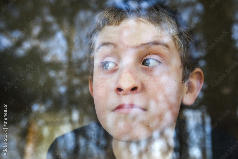 Fototapeta Boy pressing his nose on the window looking out