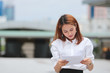 Confident young Asian business woman sitting and analyzing charts or paperwork at outdoors