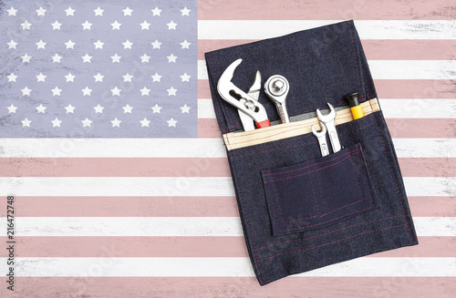 Photo  Steel tools in design pocket tool bag on abstract USA flag background, Laborday