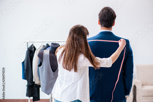 Professional tailor taking measurements for formal suit Wallpaper Mural