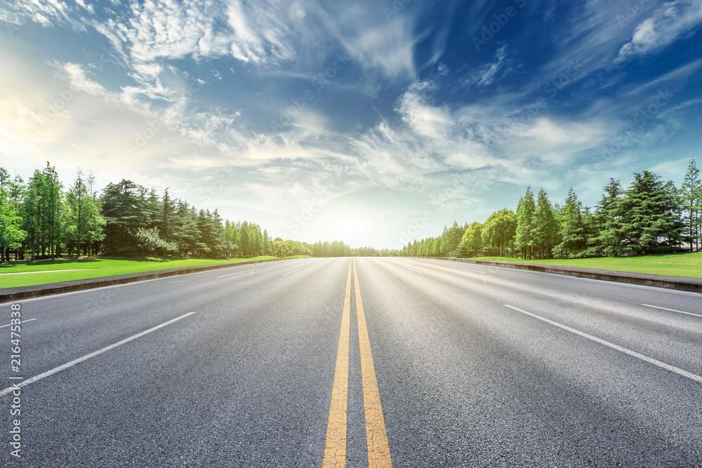 Fototapeta Asphalt road and green forest landscape under the blue sky