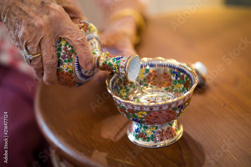Fotografie, Obraz  Buddhist's grail pouring water in thai celemony new home