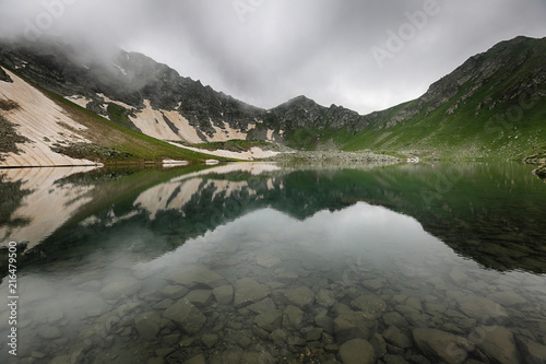 Poster Bergen Caucasus mountains reflected in lake water in foggy weather