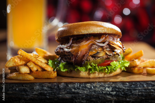 Big tasty burger and fries with beer on background on the wooden table © Yeti Studio