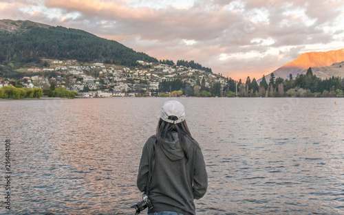 Fotobehang Nieuw Zeeland Back view of Asian tourist standing in front of the Lake Wakatipu and looking to Queenstown most tourist attraction city in South Island of New Zealand.