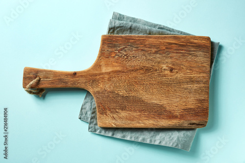 Wooden cutting board on blue background, from above