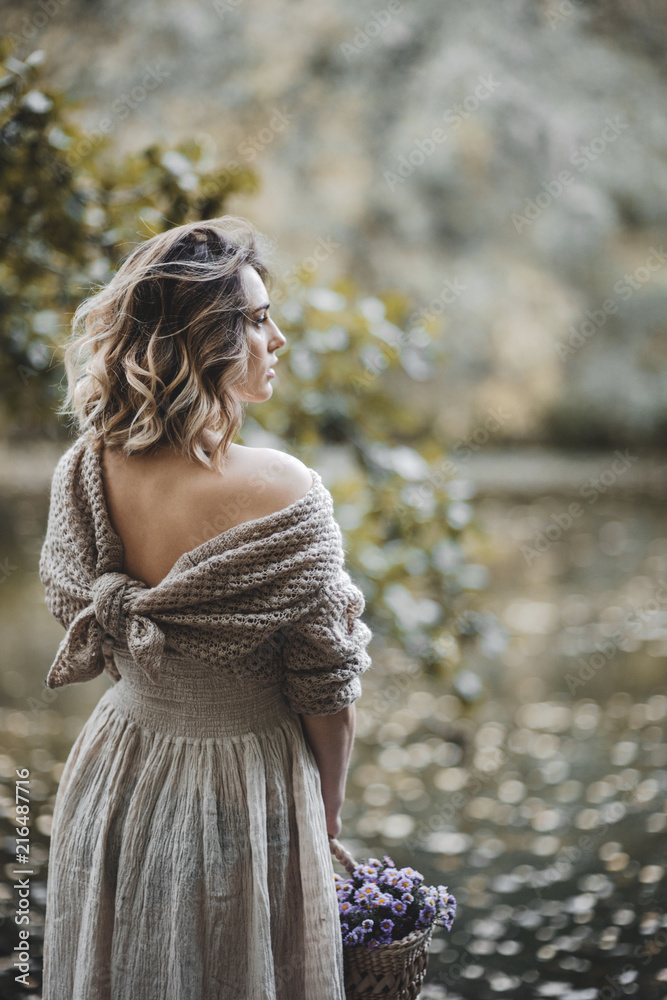 Fototapeta Romantic woman in a knit sweater near the lake in autumn park
