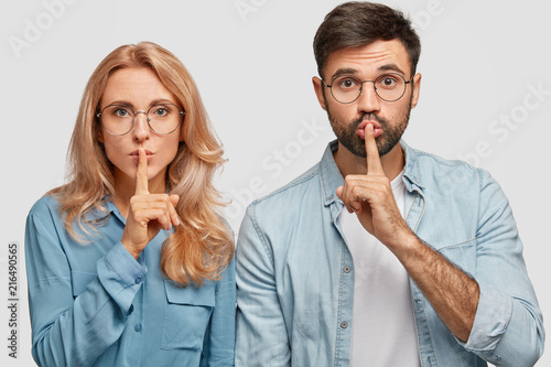 Fotografie, Obraz  Portrait of mute pretty young female and male makes hush sign, ask to be quiet, keep fore fingers on lips, stand closely, isolated over white background