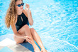 Beautiful blonde woman in good shape with long gorgeous curly hair and perfect skin in black swimming suite sitting on pool edge with blue sparkling water protecting her eyes with sunglasses.