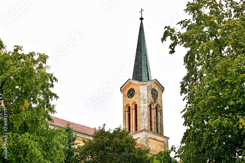 Church tower with green roof and a metal cross on the top, yellow and white pain Poster