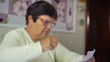 Senior Woman Putting Eyeglasse...