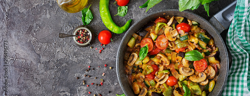 Hot spicy stew eggplant, sweet pepper, tomato, zucchini and mushrooms. Flat lay. Top view. Banner