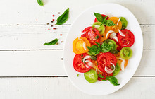 Colored Tomato Salad With Onion And Basil Pesto. Vegan Food. Top View. Flat Lay