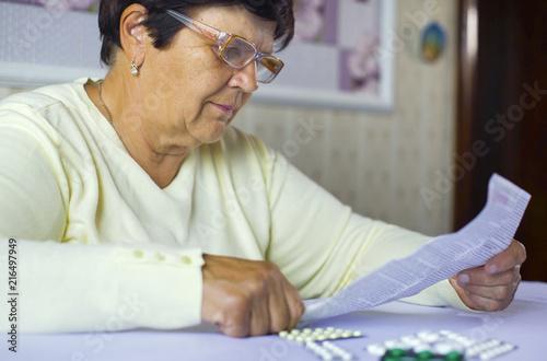 Senior woman reading information sheet of prescribed medicine sitting at table at home Fotobehang