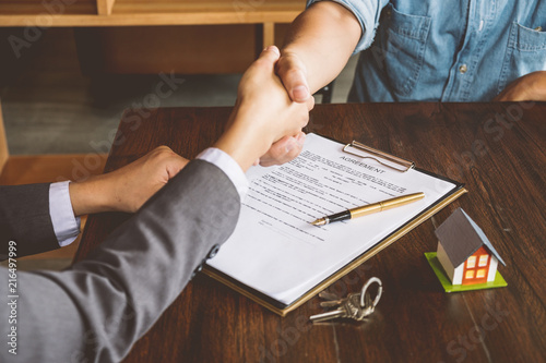 Fotografie, Obraz  Real estate broker agent shaking hands with customer after sign agreement to buy house contract,bank loan approved, mortgage investment, Real estate Concept