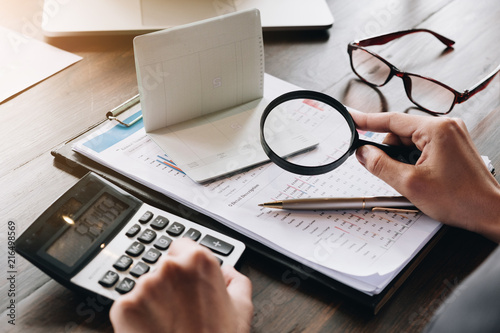 Photo An auditor hand holding magnifying glass over saving account passbook for looking and analysis financial data,  Business finances and Saving concept