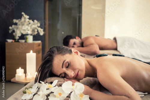 Fototapety, obrazy: Young couple relaxing under the stimulating effects of a traditional hot stone massage at luxury spa and wellness center