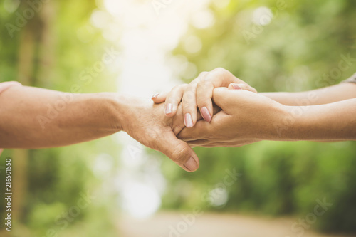 Fotografía  close-up of a daughter holding her mother's hand outdoors over nature background