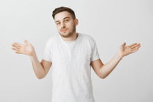 I Have No Idea Man Ask Anyone Else. Careless Relaxed Handsome Unshaven Guy With Stylish Haircut In White T-shirt Making Shoulder Shrug Gesture With Palms Spread Aside Being Clueless And Unaware